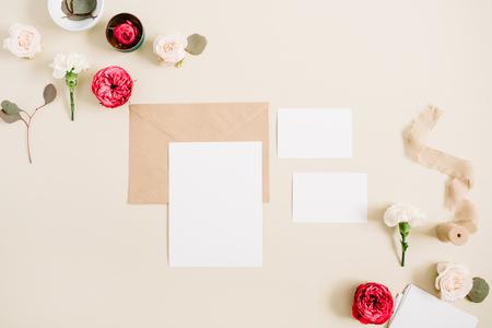De kaarten van de huwelijksuitnodiging, ambachtenvelop, roze en rood namen bloemknoppen en witte anjer op bleke pastelkleur beige achtergrond toe. Werkruimte met blanco papier. Plat leggen, bovenaanzicht