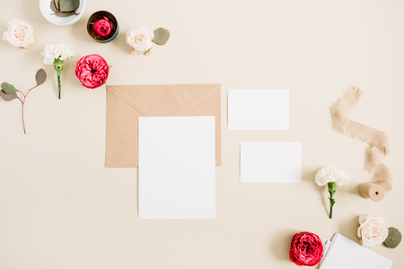 Wedding invitation cards, craft envelope, pink and red rose flower buds and white carnation on pale pastel beige background. Workspace with paper blank. Flat lay, top view