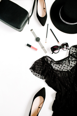 Trendy fashion black styled woman clothes and accessories collection on white background. Flat lay, top view. Dress, high heels, sunglasses, purse, watches.
