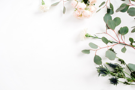 Beige rose flowers, eringium flower, eucalyptus branches on white background. Flat lay, top view. Floral background Stockfoto