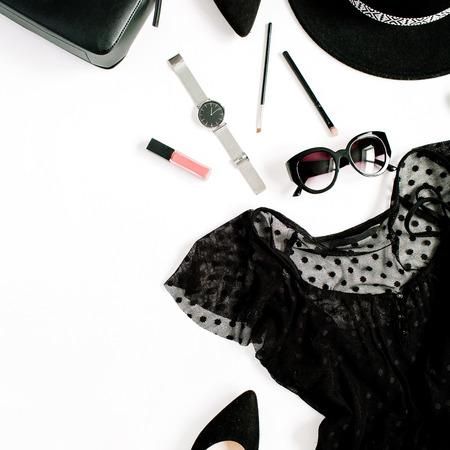 Il nero d'avanguardia di modo ha disegnato la raccolta dei vestiti e degli accessori della donna su fondo bianco. Vista piana, vista dall'alto. Vestito, tacchi alti, occhiali da sole, borsa, orologi. Archivio Fotografico - 82118337