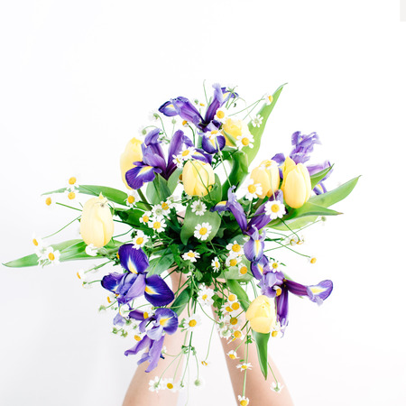Girls hands holding beautiful flowers bouquet on white background. Flat lay, top view. Floral composition 版權商用圖片
