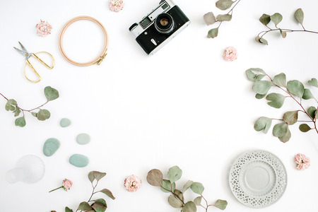 Flat lay border frame with retro camera, eucalyptus branches, plate and scissors on white background. Top view artist background with space for text. Foto de archivo