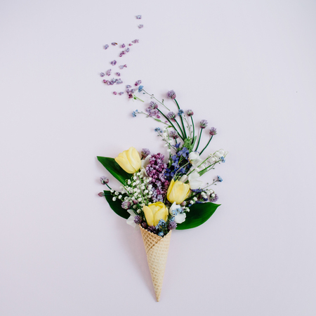Waffle cone with lilac flower, lily of the valley, tulips bouquet on background. Flat lay, top view floral background. Banco de Imagens - 83605742