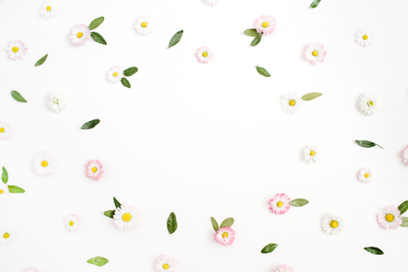 Floral frame made of white and pink chamomile daisy flowers, green leaves on white background. Flat lay, top view. Daisy background. Frame of flower buds. Banco de Imagens