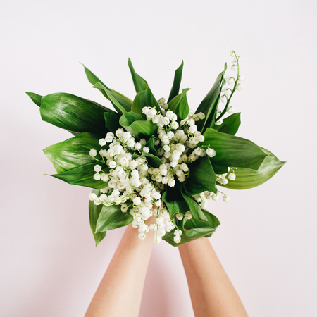 Girls hands holding white lily of the valley bouquet on pink background. Flat lay, top view.