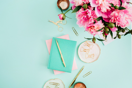 Flat lay home office desk. Female workspace with pink peony flowers bouquet, golden accessories, pink and mint diary on mint background. Top view feminine background.