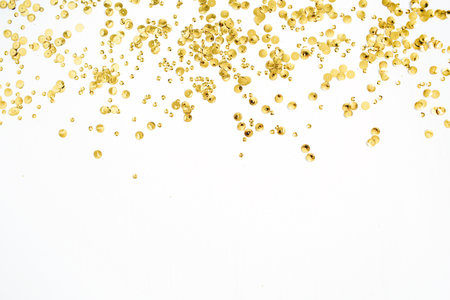 Golden confetti tinsel on white background. Flat lay, top view. Minimal background.