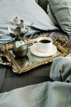 Morning coffee on golden vintage tray in bed with grey sheet and pillows.