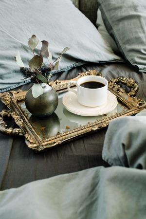 Ochtendkoffie op gouden uitstekend dienblad in bed met grijze blad en hoofdkussens.