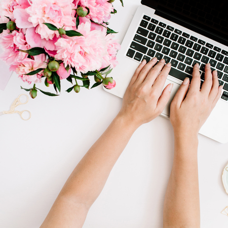 Flat lay home office desk. Workspace with girls hands, laptop, pink peony bouquet, golden accessories. Top view Stok Fotoğraf