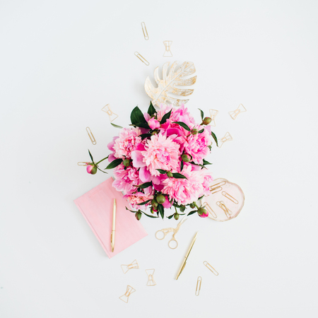Flat lay home office desk. Female workspace with pink peonies bouquet, golden accessories, pink diary on white background. Top view feminine background.