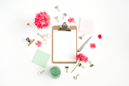 Flat lay home office desk. Clipboard with copy space for text, red flowers, accessories, mint diary on white background. Top view mock up women background. Stock Photo
