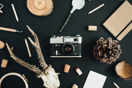 Top view, flat lay hipster photographer concept. Retro camera, goat horns, handmade spoon, craft diary, cone on black chalk board background.