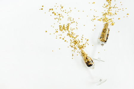 Glasses with golden confetti tinsel on white background. Flat lay, top view celebrate party concept. Archivio Fotografico