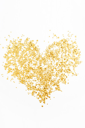 Heart made of golden confetti on white background. Flat lay, top view. Minimal love concept. Stock Photo