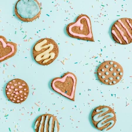 Kleurrijke handgemaakte koekjes en confetti op blauwe achtergrond. Vlak gelegen, bovenaanzicht.