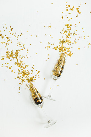 Champagne glasses with golden confetti tinsel on white background. Flat lay, top view celebrate party concept. Imagens