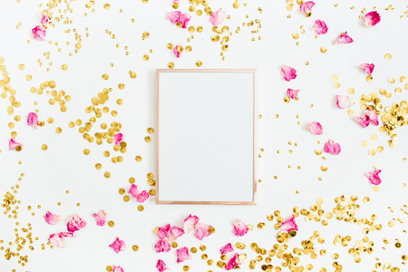 Photo frame mock up with space for text, pink rose petals and golden confetti on white background. Flat lay, top view. Valentines minimal background. Stock Photo