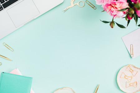 Flat lay home office desk. Female workspace with laptop, pink peonies bouquet, golden accessories, pink and mint diary on mint background. Top view feminine background. 免版税图像