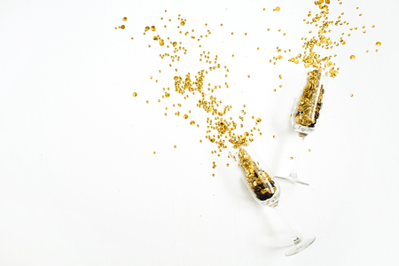Champagne glasses with golden confetti tinsel on white background. Flat lay, top view celebrate party concept. Archivio Fotografico