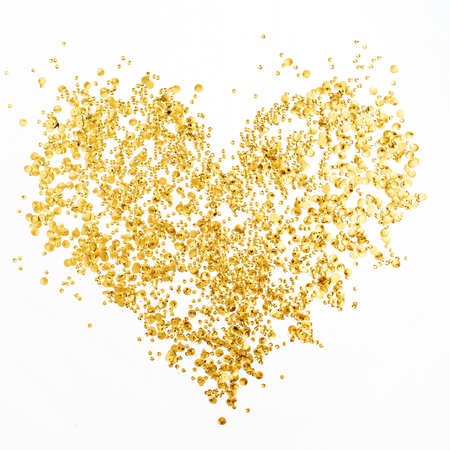 Heart made of golden confetti tinsel on white background. Flat lay, top view. Minimal love concept.