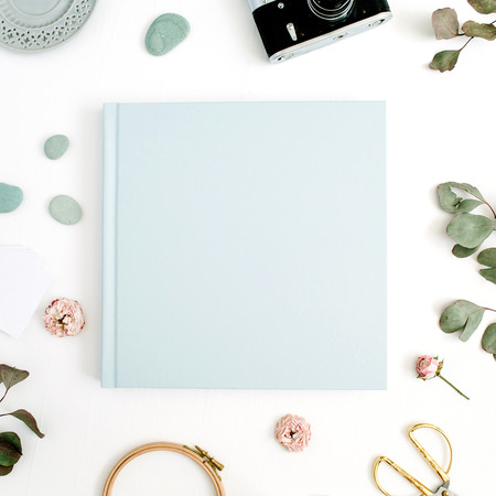 Blue family or wedding photo album  with blank space for text, eucalyptus leaf, retro camera and dry rose buds on white background. Flat lay, top view.