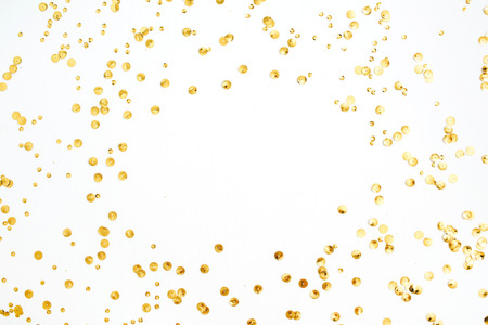 Mock up frame with space for text made of golden confetti tinsel on white background. Flat lay, top view. Minimal background.