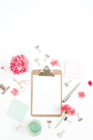 Flat lay home office desk. Clipboard with copy space for text, red flowers, accessories, mint diary on white background. Top view mock up women background. Stockfoto