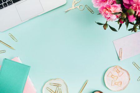 Flat lay home office desk. Female workspace with laptop, pink peonies bouquet, golden accessories, pink and mint diary on mint background. Top view feminine background. Stockfoto