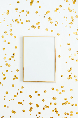 Photo frame mock up with space for text and golden confetti on white background. Flat lay, top view. Minimal background. Archivio Fotografico
