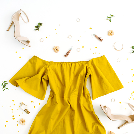 Women's fashion clothes and accessories on white background. Flat lay female golden styled look with dress, high heels, watch, bracelet. Top view.