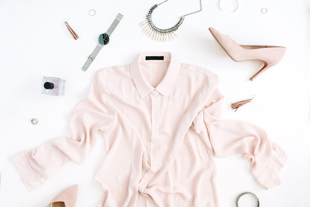 Women modern fashion clothes and accessories. Flat lay female casual style look with pastel blouse, high heels, watch, perfume. Top view. Foto de archivo