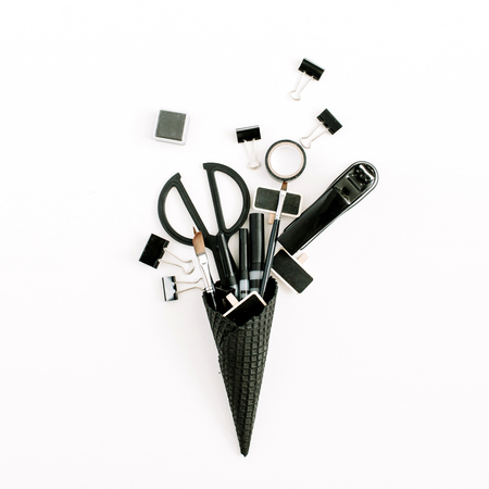 Black waffle cone with office stationery tools. Flat lay, top view minimal office concept.