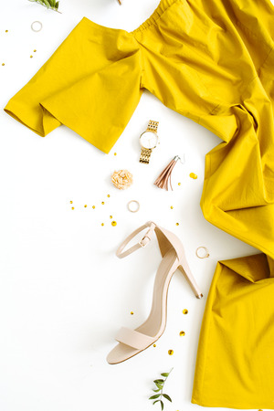 Womens fashion clothes and accessories on white background. Flat lay female golden styled look with dress, high heels, watch, bracelet. Top view. Stock Photo