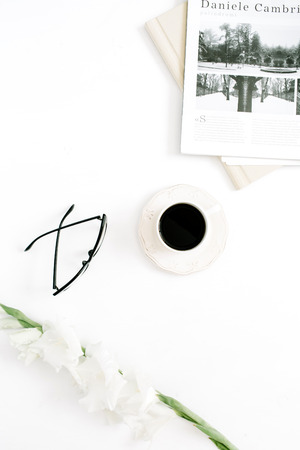 Morning coffee cup, newspaper, gladiolus flower and glasses on white background. Flat lay, top view women background.