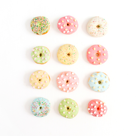 Colorful donuts on white background. Flat lay, top view minimal pattern.