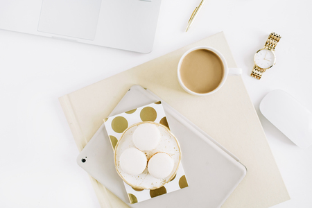 Flat lay minimal desk workspace with macaroons, coffee, feminine accessories. Top view modern minimal lifestyle concept.