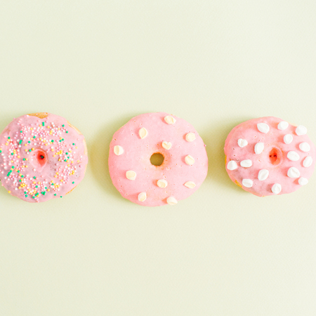 Pink donuts on green background. Flat lay, top view minimal pattern.