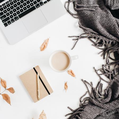 Bureaudesktop met laptop, ambachtagenda, gouden pen, badstofplaid, de herfstherfstbladeren, koffie met melk op witte achtergrond. Plat leggen, bovenaanzicht.