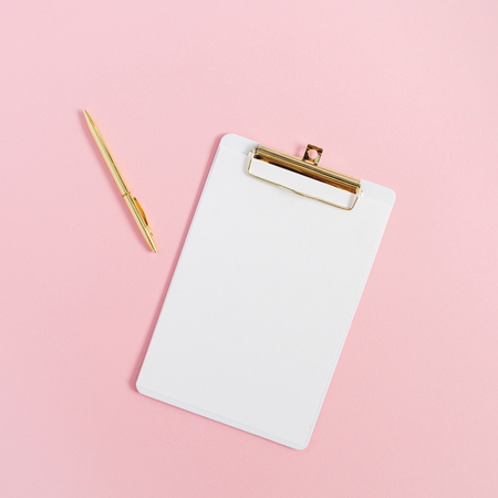 Clipboard and golden pen on pink background. Minimal flat lay mock up.