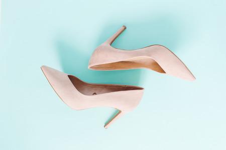 Mode-Blog-Look. Blasse rosa Frauen-Absatzschuhe auf blauem Hintergrund. Flache Lage, weiblicher Hintergrund der modischen Schönheit der Draufsicht.