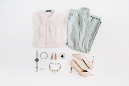 Women modern fashion clothes and accessories. Flat lay female casual style look with pastel blouse, trousers, high heels, watch, perfume, necklace, earrings. Top view.