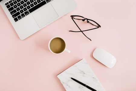 Flat lay minimal feminine workspace with laptop, marble notebook, glasses, mouse and coffee on pastel pink background. Top view.