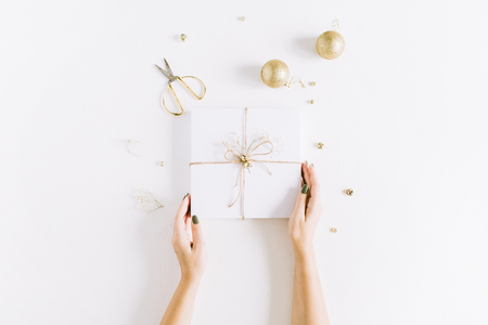 Female hands holding white gift box with bow. Christmas flat lay, top view concept.