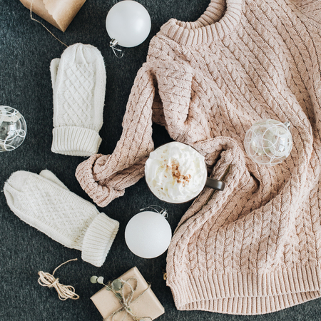 Womens winter clothes look on grey plaid. Warm beige sweater and white knitted mittens, gift box and glass balls. Christmas fashion composition. Flat lay, top view.