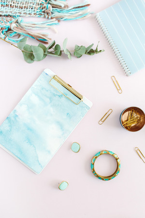 Flat lay home office desk. Female workspace with clipboard, diary, stationery on pale pink background. Top view feminine concept.