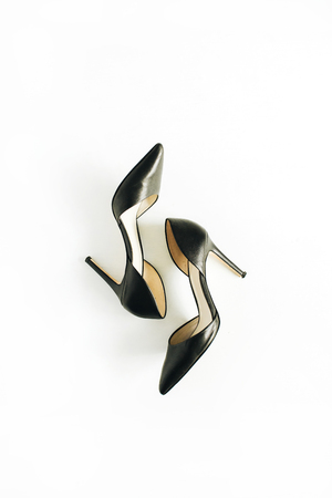 Black female high heels on white background. Flat lay, top view.