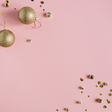 Golden confetti and Christmas toy balls on pink background. Flat lay, top view holiday background.