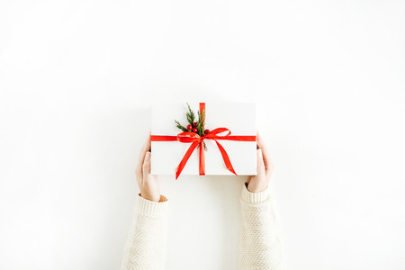 Christmas concept. Women hands holding gift box. Flat lay, top view. Imagens